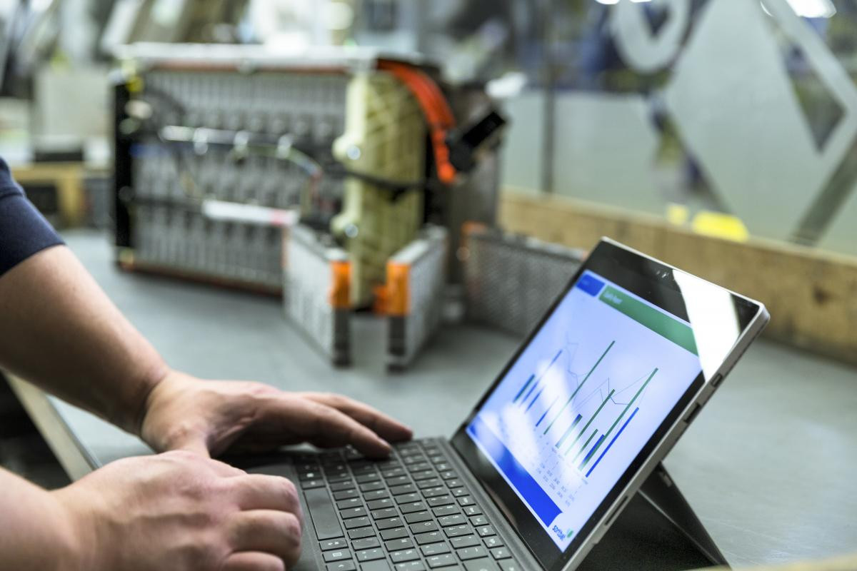 guy on computer in a car workshop