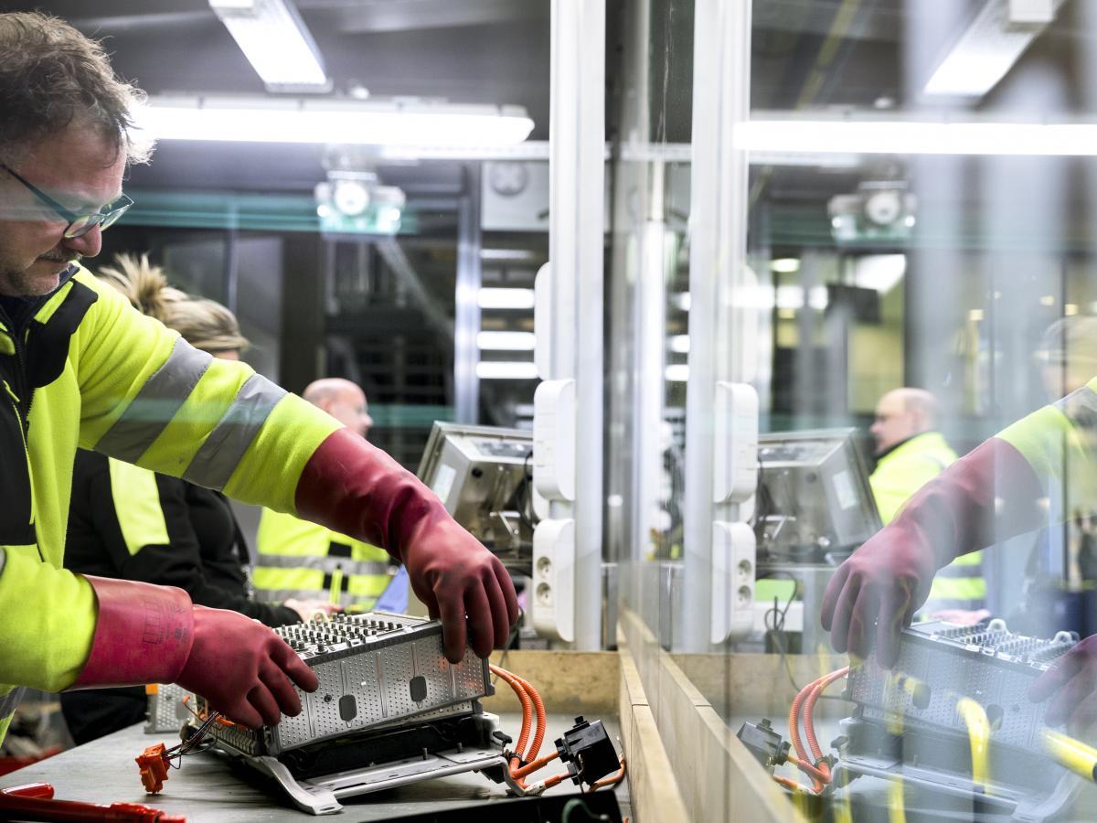 guy handling electric car batteries