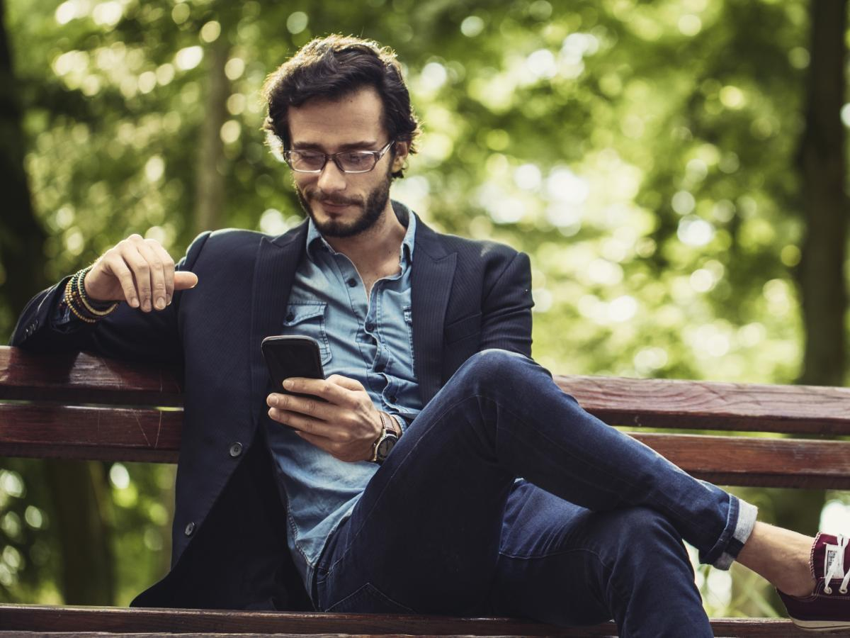 Chill guy using his phone sitting on a bench