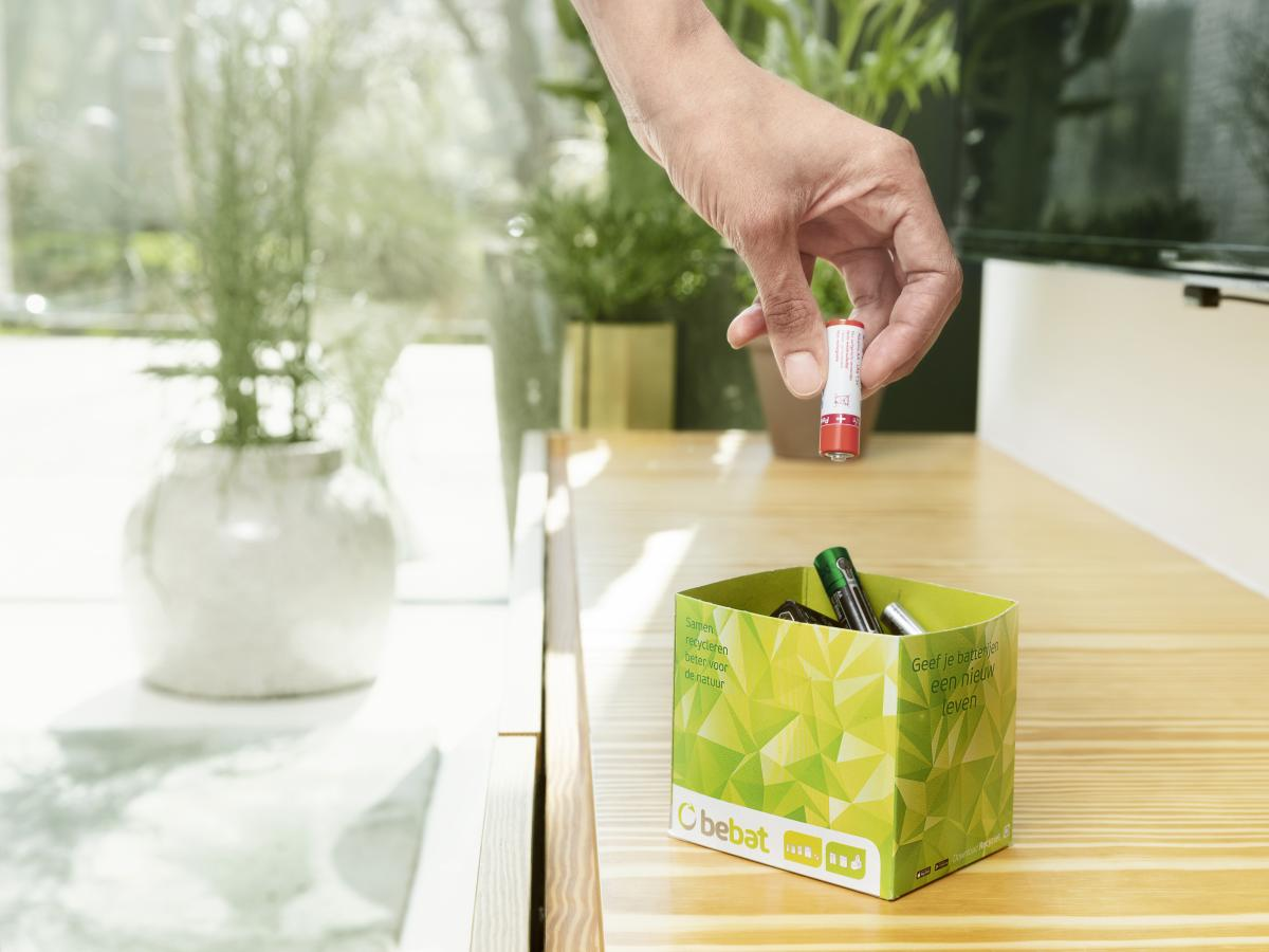 person throwing a battery in a bebat box