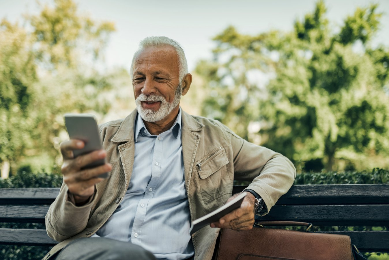 Old guy looking at his phone, sitting on a bench